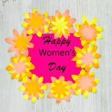 Wishing Happy Womens Day in paper flowers frame on wooden background. Flat lay royalty free stock image