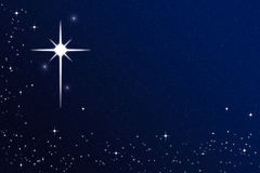 Wishing on a Starry Christmas Night Sky Star. Starry Christmas winter night sky with bright cross star. Festive,  magical, enchanting and celestial concept Stock Photo