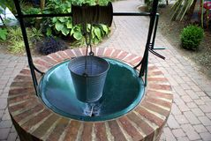 Wishing well with a bucket in a garden Stock Image