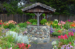 Wishing well in dahlia garden Stock Photos