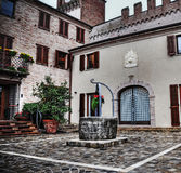 Wishing well in a small picturesque square Stock Photography