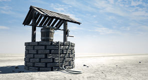 Wishing Well With Wooden Bucket On A Barren Landscape. A brick water well with a wooden roof and bucket attached to a rope in a flat barren landscape with a blue Stock Photography