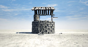 Wishing Well With Wooden Bucket On A Barren Landscape. A brick water well with a wooden roof and bucket attached to a rope in a flat barren landscape with a blue Royalty Free Stock Photography