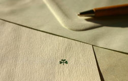 Wishing you lots of luck!. Letter paper with cloverleaf symbol, ballpoint-pen and envelope royalty free stock photo