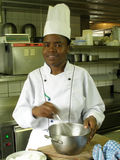 Wisking the batter. Black female chef is wisking the batter royalty free stock photo