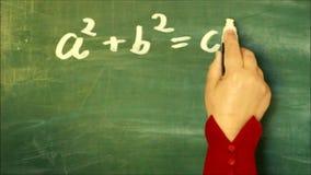 Wiskunde: Vrouwelijke hand die de stelling van Pythagoras op een bord schrijven stock video