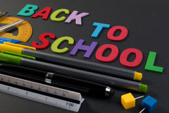 Wiskundige instrumenten over de hoek van zwart document met tekst terug naar school stock fotografie
