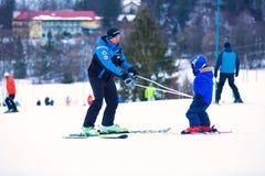 Wisla Polen, 18 02 2016 - man den undervisande lilla ungen hur man skidar H Arkivbilder