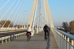 热舒夫,波兰- 9 9 2018年:有女孩乘坐的自行车的一个人在横跨Wislok河的停止路桥梁晴朗的,clea 免版税库存照片