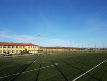 Wisniowa, Polônia - 9 9 2018: Um estádio aberto no pátio de uma escola da vila Descarga da geração mais nova Ostenta o groun foto de stock