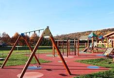 Wisniowa, Polen - 12 oct 2018: De speelplaats van kinderen in het park in het midden van groen Multicolored schommeling en gebouw stock afbeelding