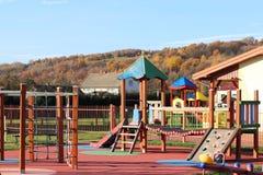 Wisniowa, Polen - 12 oct 2018: De speelplaats van kinderen in het park in het midden van groen Multicolored schommeling en gebouw royalty-vrije stock foto