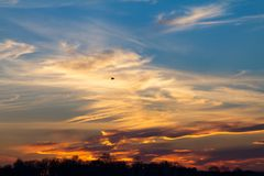 Wisps of clouds in the sky during a colorful sunset Stock Images