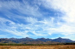 Wispy clouds above mountains Royalty Free Stock Images