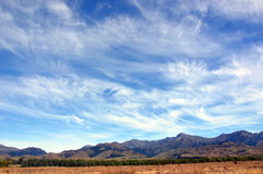 Wispy clouds in blue skies above mountain range Royalty Free Stock Photography
