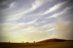 Wispy clouds over farmland Stock Images