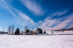 Wispy clouds over a snow covered farm in rural Carroll County, M Royalty Free Stock Photo