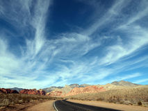 Wispy desert highway clouds. Wispy clouds over red rocks and highway in the vast deserts of Nevada, USA Royalty Free Stock Photos