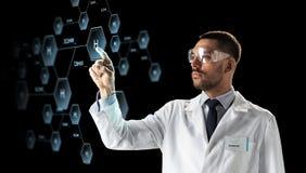 Wissenschaftler in den Schutzbrillen mit chemischer Formel Stockfoto