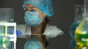 Wissenschaftler, der auf Handschuhe am Arbeitstaganfang, schützende Uniform sich setzt stock footage