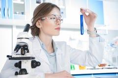 Wissenschaftler, der auf Reagenzglas schaut Lizenzfreie Stockbilder