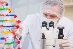 Wissenschaftler, der DNA-Helix überprüft und im Mikroskop schaut stockbilder