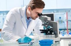 Wissenschaftler, der durch ein Mikroskop schaut Stockbild
