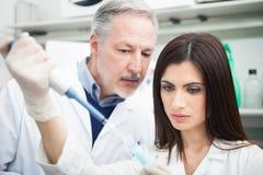 Wissenschaftler, der eine Probe von einem Reagenzglas entnimmt Lizenzfreie Stockbilder
