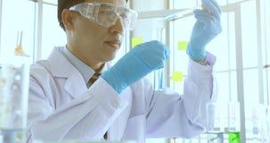 Wissenschaftler, der Experiment im Laborraum tut stock video footage
