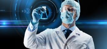 Wissenschaftler in der Maske, die Flasche mit Chemikalie hält Stockfoto
