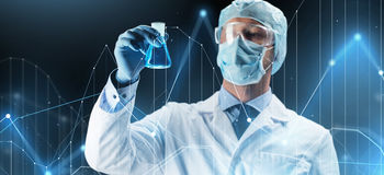 Wissenschaftler in der Maske, die Flasche mit Chemikalie hält Lizenzfreie Stockfotografie