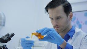 Wissenschaftler der medizinischen Forschung mischt rauchende Mittel in einer Petrischale stock footage