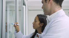 Wissenschaftler der medizinischen Forschung schreibt wissenschaftliche Formel auf ein Glas-whiteboard stock video footage
