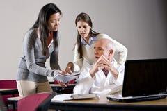 Wissenschaftler, der mit Assistenten im Konferenzsaal spricht Stockfoto