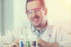 Wissenschaftler, der Reagenzgläser mit Chemikalien betrachtet Lizenzfreie Stockbilder
