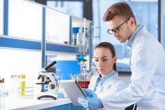 Wissenschaftler, die digitale Tablette für Analyse im Labor verwenden Stockbilder