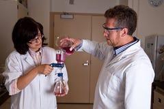 Wissenschaftler, die labware anhalten Lizenzfreies Stockbild