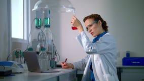 Wissenschaftler finden eine Heilung Frauenwissenschaftler, der chemische Flüssigkeit in der Laborflasche betrachtet stock footage