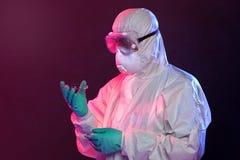 Wissenschaftler in Hazmat-Klage, die Petri Dish hält Stockfotos