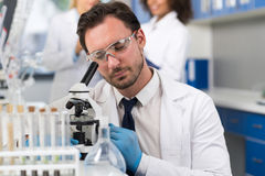 Wissenschaftler Looking Through Microscope im Labor, männlicher Forscher Doing Research Experiments stockfotografie
