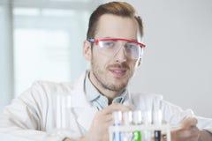 Wissenschaftler mit Reagenzgläsern in den Schutzbrillen Stockbild