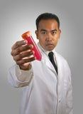 Wissenschaftler mit Reagenzglas-leuchtender Steigung BG Stockfoto