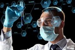 Wissenschaftler mit Reagenzglas und chemischer Formel Lizenzfreies Stockfoto