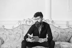 Wissenschaftler, Professor auf durchdachtem Gesicht genießen Literatur Lektor sitzen auf Sofa und Lesebuch, weißer Wandhintergrun stockfotografie