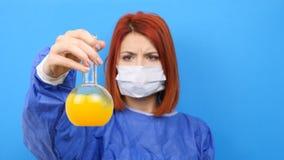 Wissenschaftlerfrau, die einen Maskenaufstieg ein Rohr mit gelber Flüssigkeit trägt stock video footage