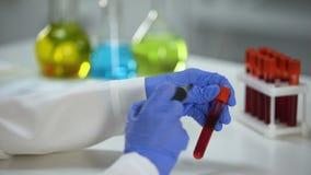 Wissenschaftlermarkierungsrohr mit roter Substanz, Blutuntersuchung, Impfstoffentwicklung stock footage