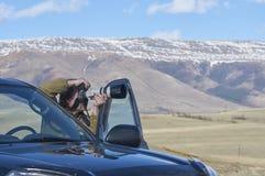 Wissenschaftlerphotograph, der auf einen Hügel steht Stockfotografie