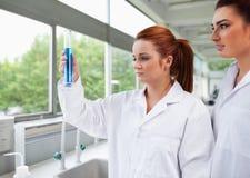 Wissenschaftskursteilnehmer, die einen abgestuften Zylinder betrachten Lizenzfreies Stockbild