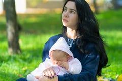 Wistful να φανεί μητέρα με το μωρό στο πολύβλαστο πάρκο στοκ εικόνες