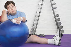 Wistful υπέρβαρο άτομο στο πάτωμα με τη σφαίρα άσκησης στοκ εικόνες